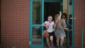 Cuatro alumnos se están divirtiendo después de lecciones de la escuela Llevan el uniforme escolar La construcción de escuelas est metrajes