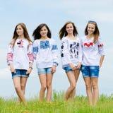 Cuatro amigas adolescentes sonrientes felices que presentan en blusas hechas a mano contra el cielo azul Fotografía de archivo libre de regalías