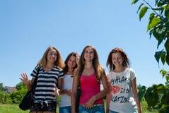 Cuatro amigas felices de las mujeres jovenes que caminan junto contra el cielo azul Imagen de archivo