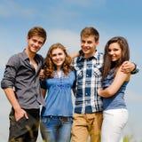 Cuatro amigos adolescentes felices al aire libre Fotos de archivo libres de regalías