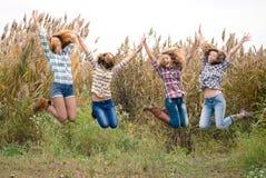 Cuatro amigos adolescentes felices al aire libre que saltan Imagen de archivo