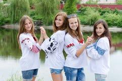 Cuatro amigos adolescentes felices de las mujeres jovenes del smilng que presentan en blusa hecha a mano Foto de archivo