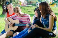 Cuatro amigos adolescentes felices que tocan la guitarra en parque verde del verano Fotos de archivo