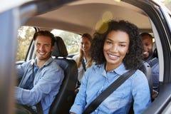 Cuatro amigos adultos en un coche en un viaje por carretera que sonríen a la cámara Foto de archivo libre de regalías