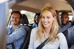 Cuatro amigos adultos en un coche en un viaje por carretera que sonríen a la cámara Fotos de archivo