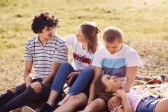 Cuatro amigos alegres tienen expresiones alegres, pasan tiempo libre en campo verde, hablan con uno a, celebran pasado con éxito foto de archivo libre de regalías