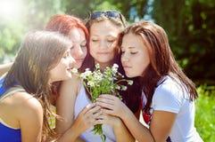 Cuatro amigos bonitos felices que juegan con las flores adentro Foto de archivo libre de regalías