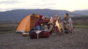 Cuatro amigos caucásicos que tienen resto cerca de la tienda turística con la hoguera en la cual frió las salchichas en montañas  almacen de video