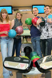 Cuatro amigos colocan el bowling de bolo cercano con las bolas Imágenes de archivo libres de regalías