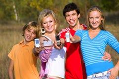 Cuatro amigos con los teléfonos móviles Fotos de archivo libres de regalías