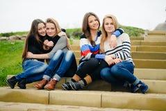 Cuatro amigos de muchachas adolescentes felices abrazan y divirtiéndose Foto de archivo libre de regalías