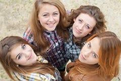 Cuatro amigos de muchachas adolescentes felices que miran para arriba Foto de archivo libre de regalías