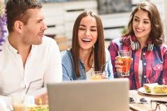 Cuatro amigos en cafetería usando el ordenador portátil Fotografía de archivo