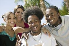 Cuatro amigos en el patio trasero que mira la cámara de vídeo defienden vista delantera Foto de archivo libre de regalías