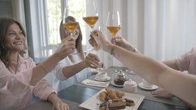 Cuatro amigos en restaurante tintinean los vidrios de vino para la reunión metrajes