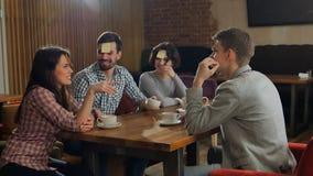 Cuatro amigos están jugando juntos quién soy en café Imagenes de archivo