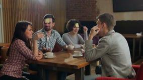 Cuatro amigos están jugando juntos quién soy en café almacen de metraje de vídeo
