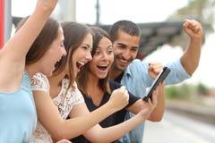 Cuatro amigos eufóricos que miran una tableta Imágenes de archivo libres de regalías