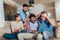 Cuatro amigos felices casuales que r?en hacer compras en l?nea junto en una tableta que se sienta en un sof? en la sala de estar fotos de archivo