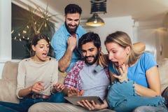 Cuatro amigos felices casuales que r?en hacer compras en l?nea junto en una tableta que se sienta en un sof? en la sala de estar foto de archivo libre de regalías