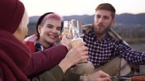 Cuatro amigos felices que tienen resto después de caminar en la montaña metrajes