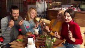 Cuatro amigos felices se divierten en un café con los cuchillos y las bifurcaciones, comen las hamburguesas almacen de metraje de vídeo