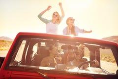Cuatro amigos femeninos en el viaje por carretera que se coloca en coche convertible Foto de archivo libre de regalías