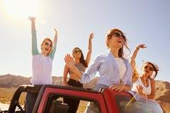 Cuatro amigos femeninos en el viaje por carretera que se coloca en coche convertible fotos de archivo libres de regalías