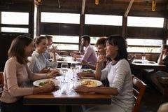 Cuatro amigos femeninos en un ½ del ¿del girlsï almuerzan en un restaurante ocupado fotografía de archivo libre de regalías