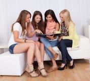 Cuatro amigos femeninos que miran una carpeta Imágenes de archivo libres de regalías