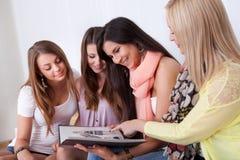 Cuatro amigos femeninos que miran una carpeta Foto de archivo libre de regalías