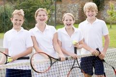 Cuatro amigos jovenes en la sonrisa del campo de tenis Foto de archivo