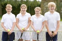 Cuatro amigos jovenes en la sonrisa del campo de tenis Foto de archivo libre de regalías