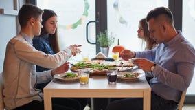 Cuatro amigos jovenes están hablando durante una comida con la pizza grande en un restaurante almacen de metraje de vídeo