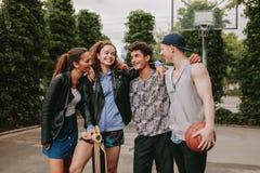 Cuatro amigos jovenes que se unen al aire libre Foto de archivo libre de regalías