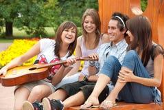 Cuatro amigos jovenes tocan la guitarra Fotografía de archivo