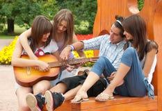 Cuatro amigos jovenes tocan la guitarra Foto de archivo