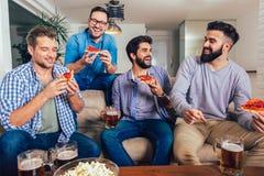 Cuatro amigos masculinos que beben la cerveza y que comen la pizza en casa fotos de archivo libres de regalías