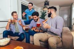 Cuatro amigos masculinos que beben la cerveza y que comen la pizza en casa foto de archivo