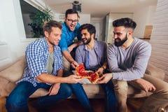 Cuatro amigos masculinos que comen la pizza en casa foto de archivo libre de regalías