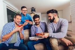 Cuatro amigos masculinos que comen la pizza en casa imagen de archivo libre de regalías