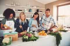 Cuatro amigos mezclados que preparan una comida en cocina Foto de archivo libre de regalías