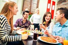 Cuatro amigos que almuerzan en un restaurante Imagenes de archivo