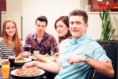 Cuatro amigos que almuerzan en un restaurante Fotos de archivo libres de regalías