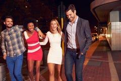 Cuatro amigos que caminan a través de ciudad junto en la noche Foto de archivo libre de regalías