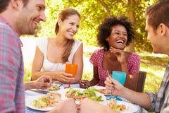 Cuatro amigos que comen junto al aire libre Imagen de archivo libre de regalías