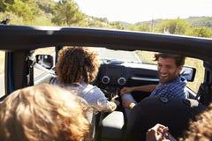 Cuatro amigos que conducen en un coche de tragante abierto, visión elevada Fotos de archivo