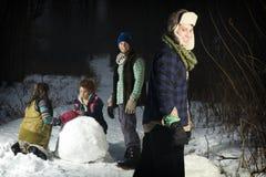 Cuatro amigos que hacen bolas de nieve en bosque Foto de archivo libre de regalías