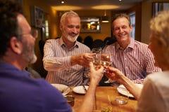 Cuatro amigos que hacen una tostada durante una comida en un restaurante Foto de archivo