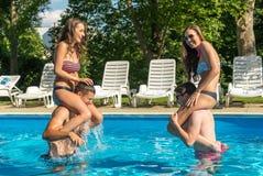 Cuatro amigos que se divierten en la piscina Fotografía de archivo libre de regalías